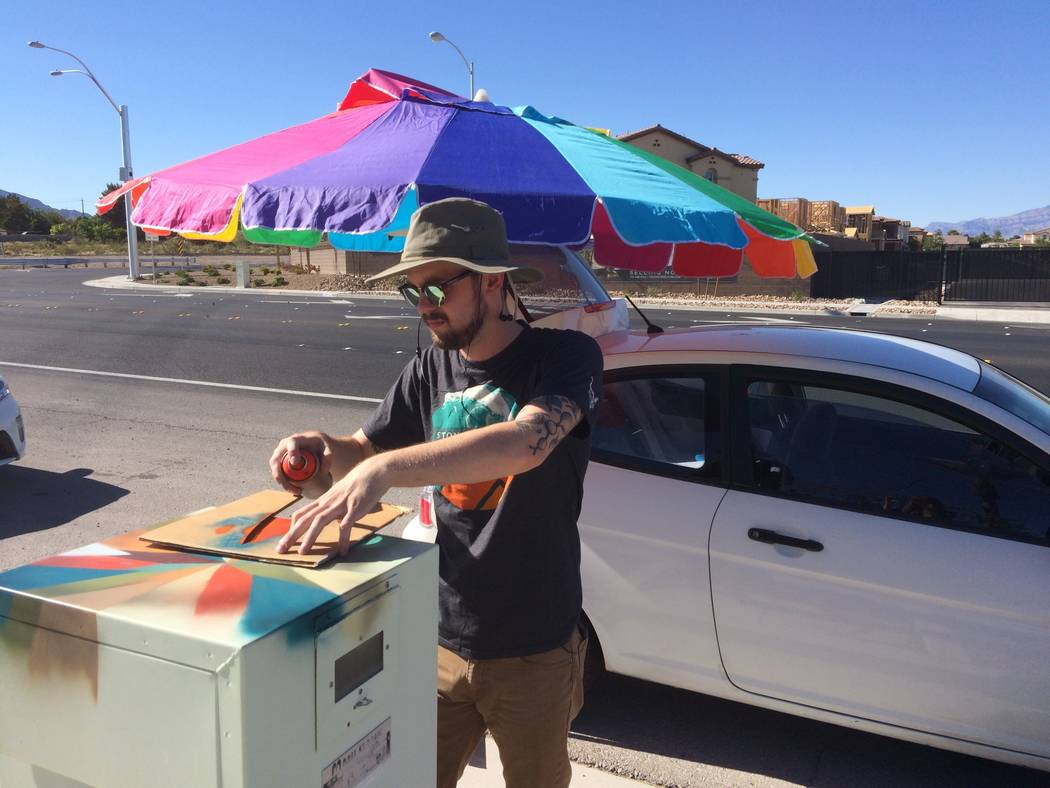 Spencer Olsen uses spray paint to create patterns on a utility box near Fort Apache and Lone Mountain roads. He is one of 15 artists who have been commissioned to make the drab gray electrical uni ...