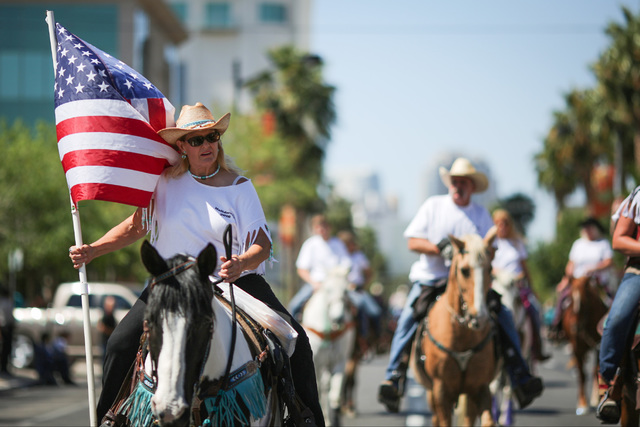 A parade participant carries an American flag while riding horseback during the 2016 Helldorado parade in downtown Las Vegas on Saturday, May 14, 2016. (Brett Le Blanc/Las Vegas) Follow @bleblancphoto