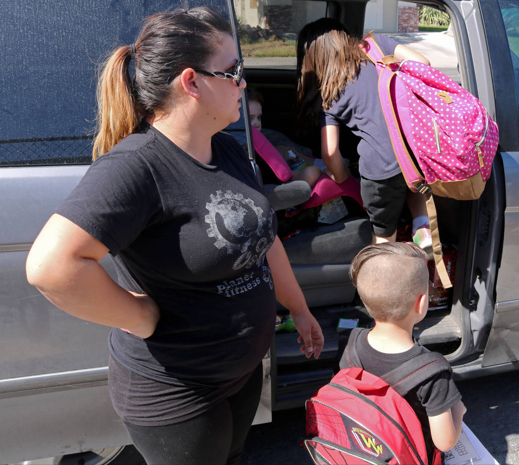 Bri-Ann Szelestey, left, ushers her children Christian, 5, foreground, and Bailey, 8, into her car at Ruth Fyfe Elementary School, Thursday, May 11, 2017. Gabriella Benavidez Las Vegas Review-Jour ...