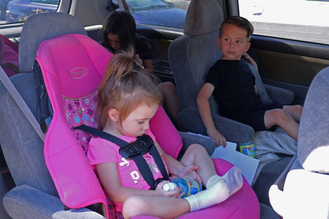 Lexie  Szelestey, 2, left, waits as her brother Christian, 5, and sister Bailey, 8, background, buckle up after getting into their mother's car at Ruth Fyfe Elementary School, Thursday, May 11, 20 ...