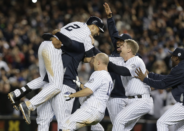 New York Yankees' Derek Jeter (2) is mobbed by teammates after driving in the winning run with a single against the Baltimore Orioles in the ninth inning of a baseball game, Thursday, Sept. 25, 20 ...
