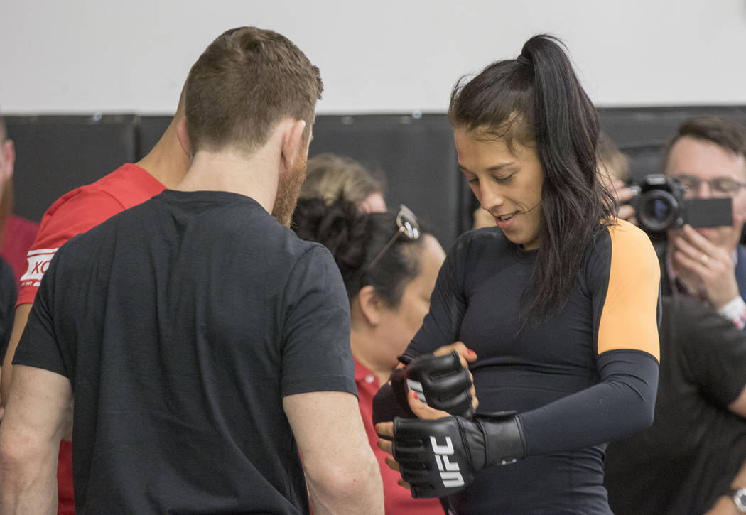 UFC women's strawweight champion Joanna Jedrzejczyk puts on her gloves at UFC 211 open workouts at the Mohler MMA gym in Dallas, Texas, on Thursday, May 11, 2017. Heidi Fang/Las Vegas Review-Journ ...