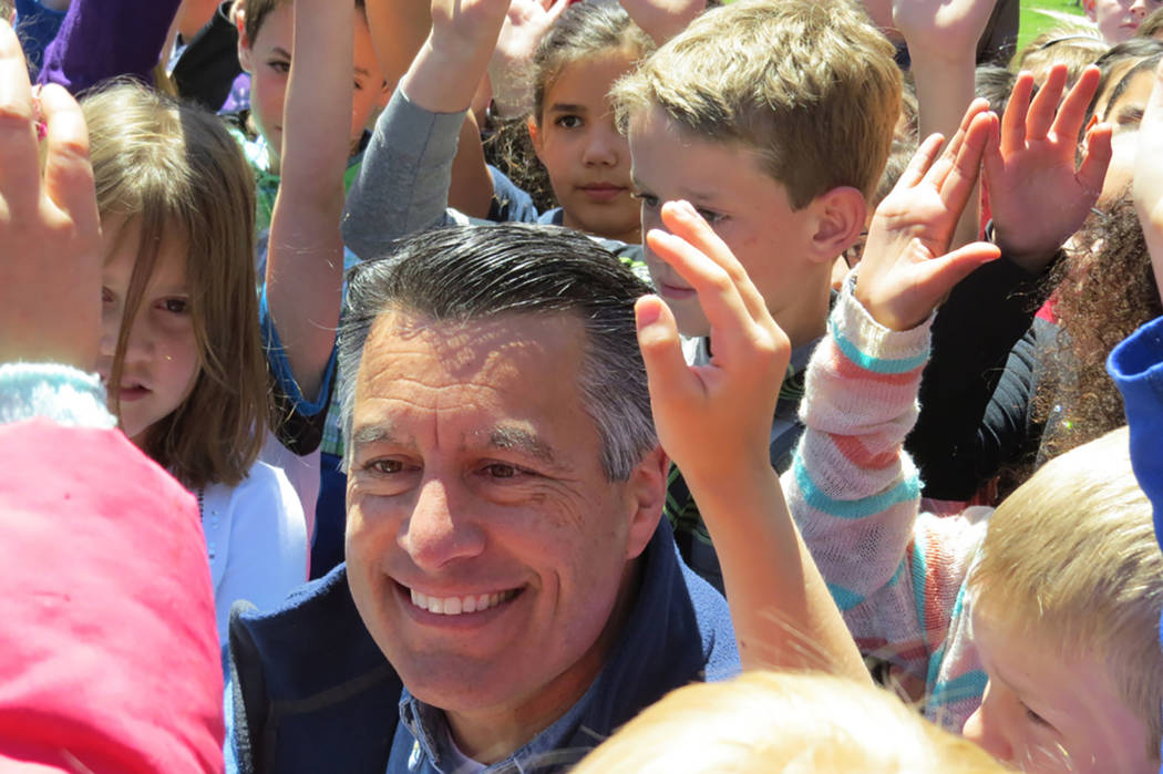 "Gov. Brian Sandoval is surrounded by young faces after signing Assembly Bill 385 at a signing ceremony in Genoa on Friday, May 12, 2017. The ""Kids in Parks"" law gives every Nevada fifth-grader, an ..."