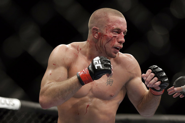 Georges St. Pierre, of Canada, fights Johny Hendricks during a UFC 167 mixed martial arts championship welterweight bout on Saturday, Nov. 16, 2013, in Las Vegas. (AP Photo/Isaac Brekken)