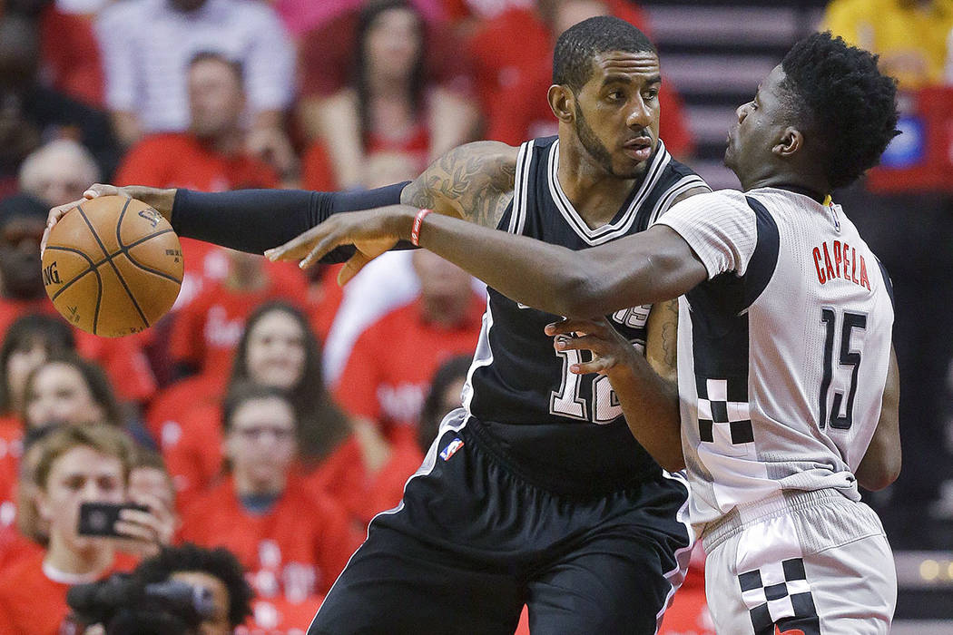 San Antonio Spurs forward LaMarcus Aldridge, left, dribbles as Houston Rockets center Clint Capela defends during the first half in Game 6 of an NBA basketball second-round playoff series, Thursda ...