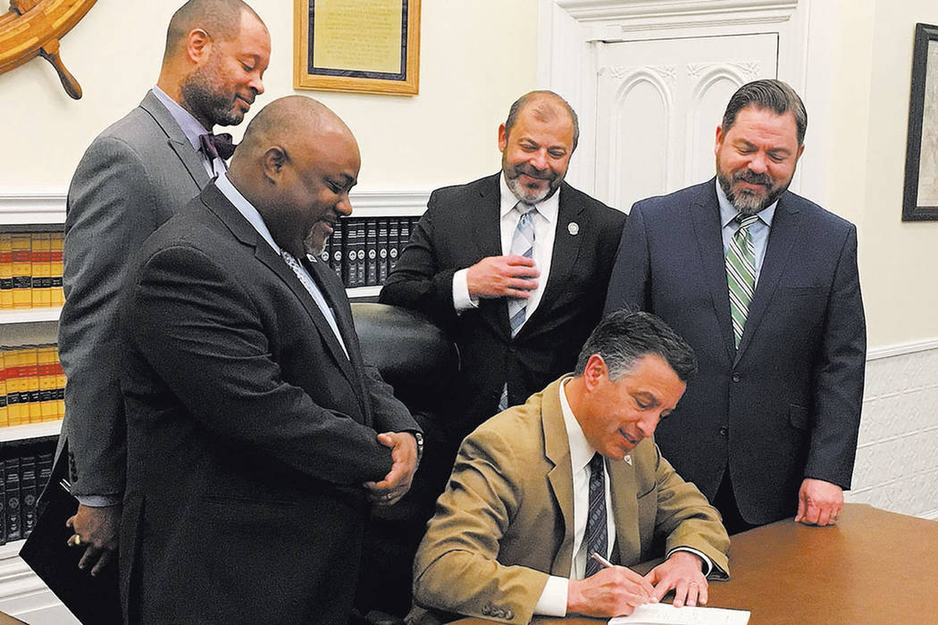 Gov. Brian Sandoval signs into law a bipartisan bill on May 8, ensuring the continued reorganization of the Clark County School District. Attending the ceremony in Carson City were, from left, Sen ...