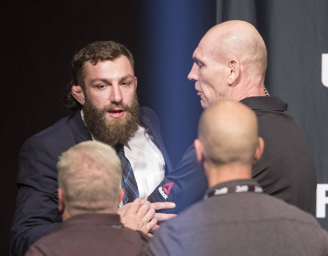UFC lightweight Michael Chiesa is escorted off the stage after an altercation with Kevin Lee, not pictured, at the UFC summer kickoff press conference at the American Airlines Center in Dallas, Te ...