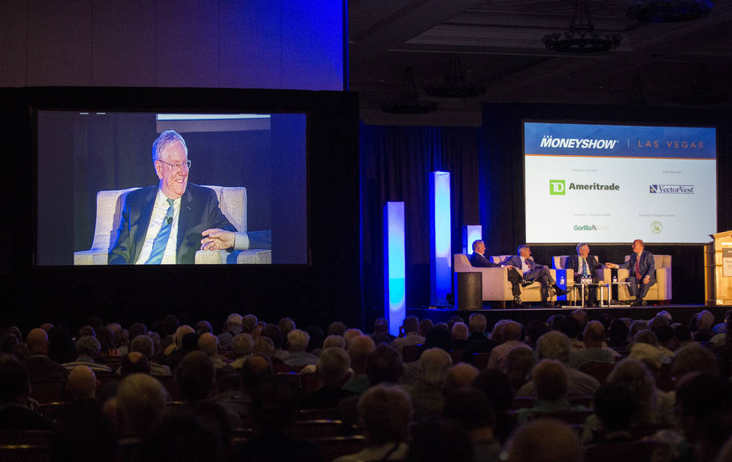 Publisher Steve Forbes, second from left and economist Mark Skousen, right, share a moment during a panel discussion as a part of the MoneyShow at Caesars Palace in Las Vegas on Monday, May 15, 20 ...