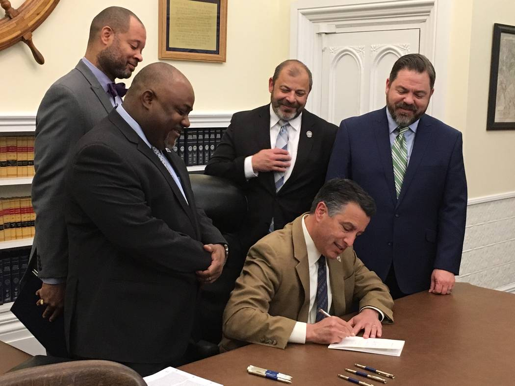 Gov. Brian Sandoval signs into law a bipartisan bill on Monday, May 8, 2017, ensuring the continued reorganization of the Clark County School District, begun in the 2015 session. Attending the cer ...