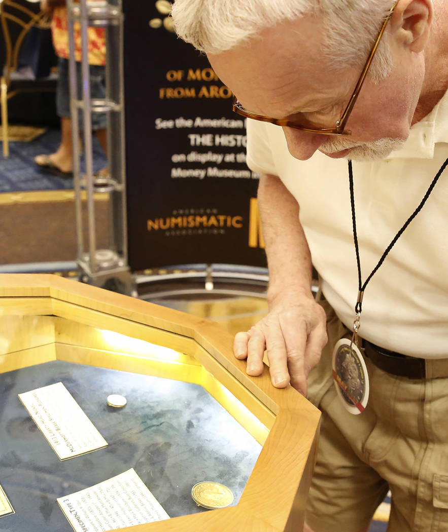 James Patton, takes a closer look at the 1804 Silver Dollar and the 1913 Liberty Head Nickel during the 54th Annual Las Vegas Numismatic Society Coin Show at Westgate hotel-casino on Thursday, May ...