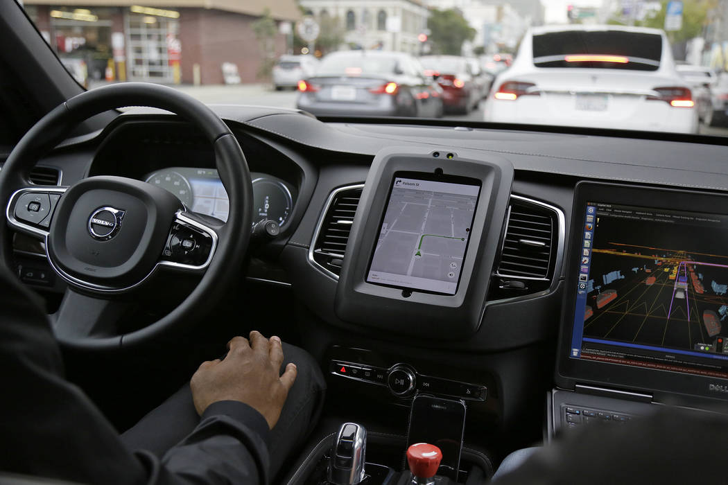 An Uber driverless car waits in traffic during a test drive in San Francisco on Tuesday, Dec. 13, 2016. In just a few years, well-mannered self-driving robotaxis will share the roads with reckless ...