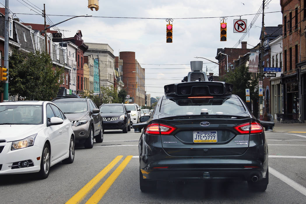A self-driving Uber car stops at a red light on Liberty Avenue through the Bloomfield neighborhood of Pittsburgh on Wednesday, Sept. 14, 2016. (Gene J. Puskar/AP)