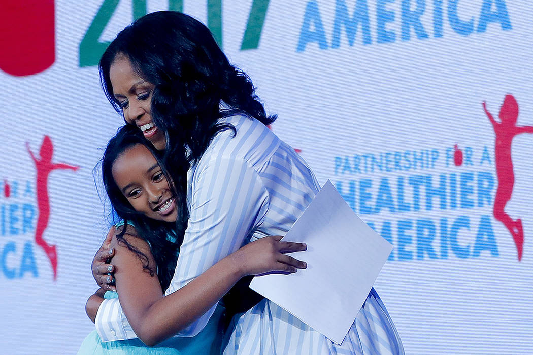 Former first lady Michelle Obama, hugs Bruktawit Tesfaye, 11, a 5th grade student from Capital City Public Charter School in Washington, who introduced Obama at the Partnership for a Healthier Ame ...