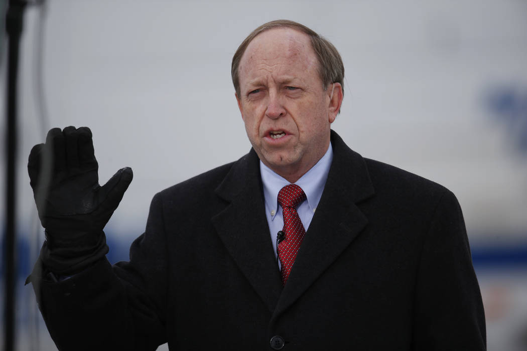In this Nov. 29, 2015, file photo, Colorado Springs, Colo., Mayor John Suthers talks to a reporter as police investigators gather evidence near the scene of Friday's shooting at a Planned Parentho ...
