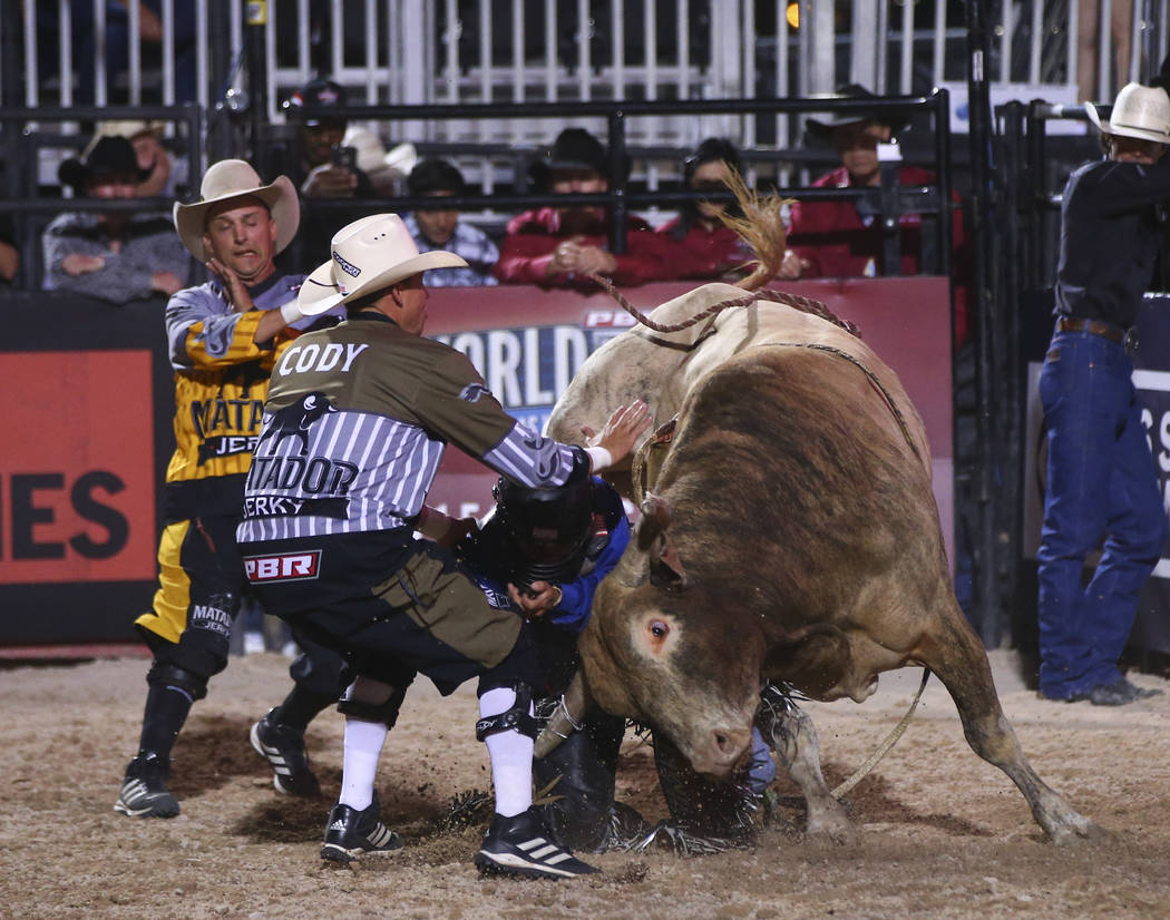 Professional Bull Riders bullfighters, Frank Newsom, left, and Cody Webster work to save Rubens Barbosa after he was bucked off of Ol' Rusty Boy during the Last Cowboy Standing event at Las Vegas  ...