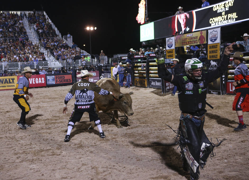 Professional Bull Riders bullfighters Frank Newsom, left, and Cody Webster distract Cowboy Phil after a successful right by Gage Gay, right, during the Last Cowboy Standing event at Las Vegas Vill ...