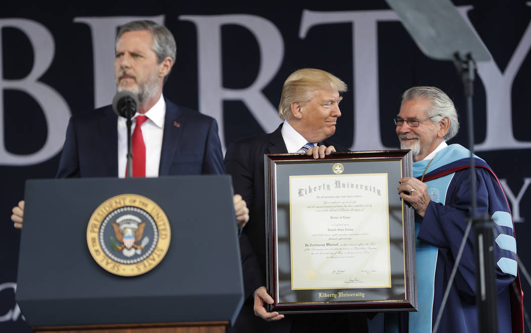 President Donald Trump, center, is presented an Honorary Degree by Ronald E. Hawkins, right, Provost and Chief Academic Officer, before giving the commencement address for the Class of 2017 at Lib ...