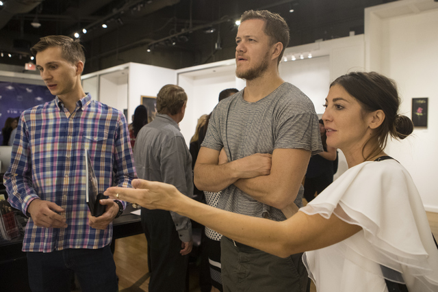 Lukas Vanagaitis, from left, Imagine Dragons band member Dan Reynolds and his wife, Aja Volkman attend Tim Cantor's exhibition at the AFA Gallery in the Fashion Show Mall in Las Vegas on Saturday, ...