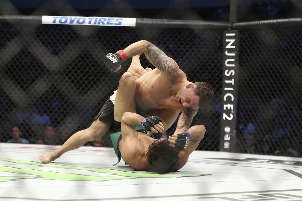 Frankie Edgar, top, fights Yair Rodriguez in a mixed martial arts bout at UFC 211 on Saturday, May 13, 2017, in Dallas. Edgar won by doctor stoppage after round 2. (AP Photo/Gregory Payan)