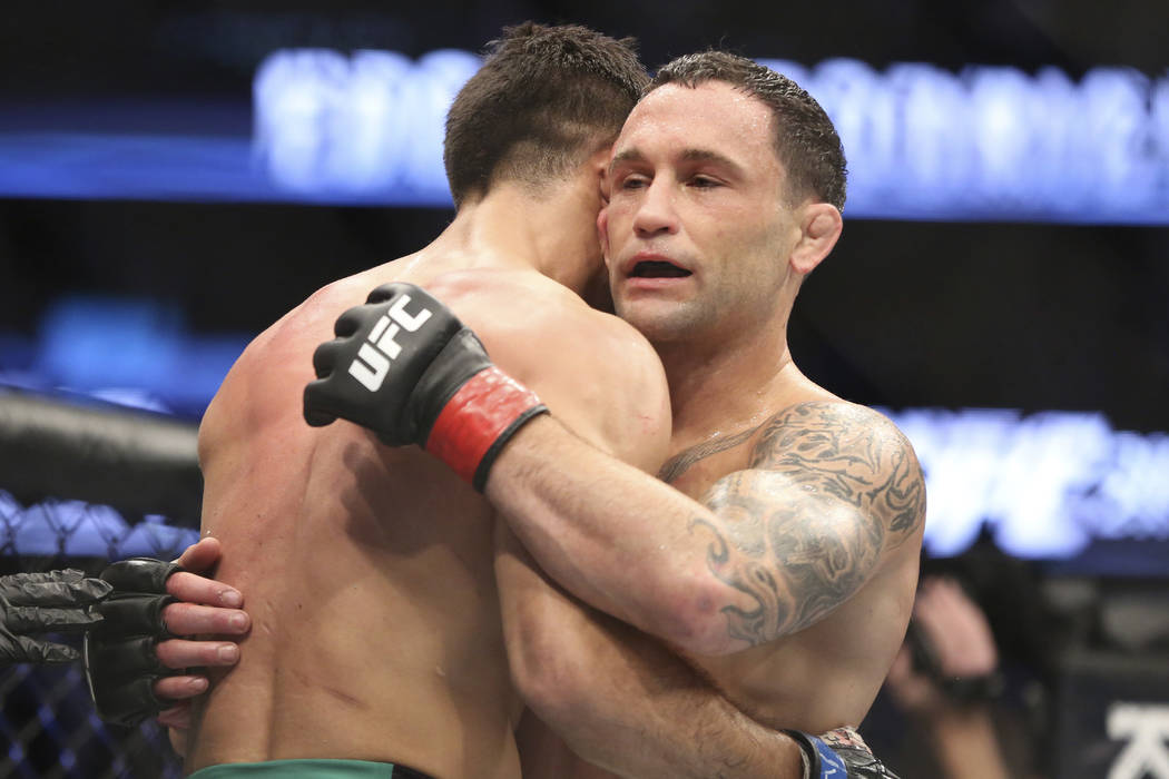 Frankie Edgar hugs Yair Rodriguez after their mixed martial arts bout at UFC 211 on Saturday, May 13, 2017, in Dallas. Edgar won by doctor stoppage after round 2. (AP Photo/Gregory Payan)