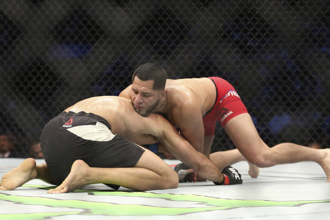 Demian Maia, bottom, fights Jorge Masvidal in a mixed martial arts bout at UFC 211 on Saturday, May 13, 2017, in Dallas. Maia won via split decision. (AP Photo/Gregory Payan)