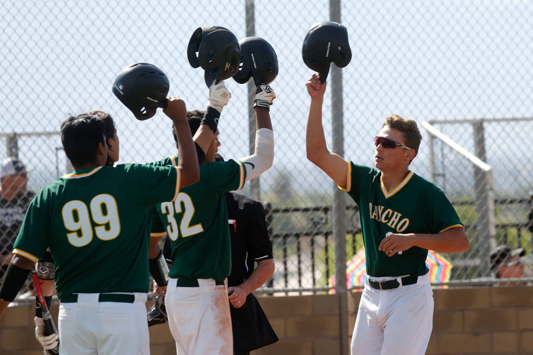 Rancho's Joseph Walls, right, celebrates with his teammates Jimmy Gamboa (99) and Edarian Williams (32) after scoring in the first inning of a state play-in baseball game against Centennial at Las ...