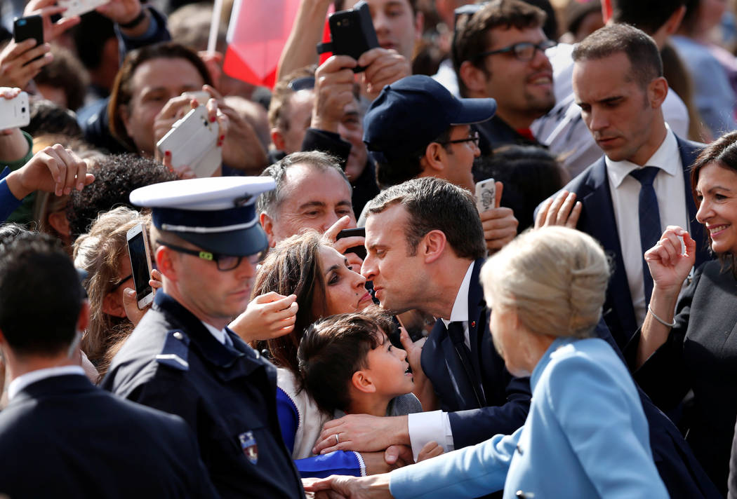 French President Emmanuel Macron, center; his wife, Brigitte Trogneux; and Paris Mayor Anne Hidalgo, right; greet people in the crowd outside the Hotel de Ville in Paris, France, May 14, 2017. (Fr ...