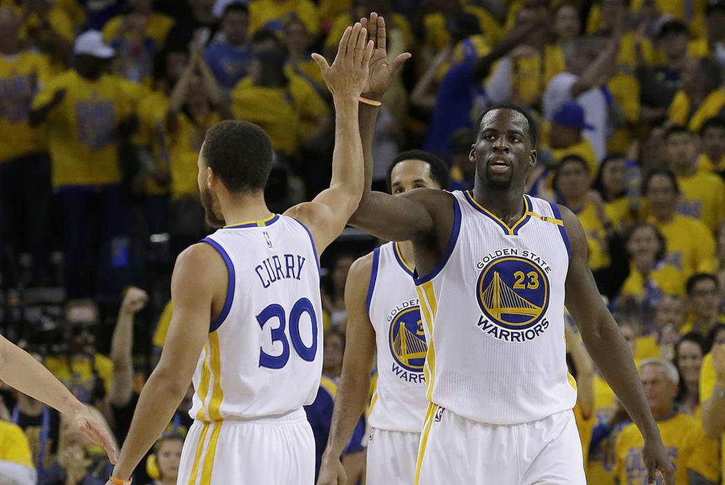 Golden State Warriors guard Stephen Curry (30) and forward Draymond Green (23) celebrate during the second half of Game 1 of the NBA basketball Western Conference finals against the San Antonio Sp ...
