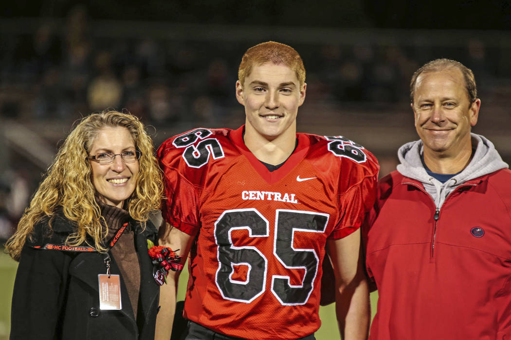 This Oct. 31, 2014, file photo provided by Patrick Carns shows Timothy Piazza, center, with his parents Evelyn Piazza, left, and James Piazza, right, during Hunterdon Central Regional High School  ...
