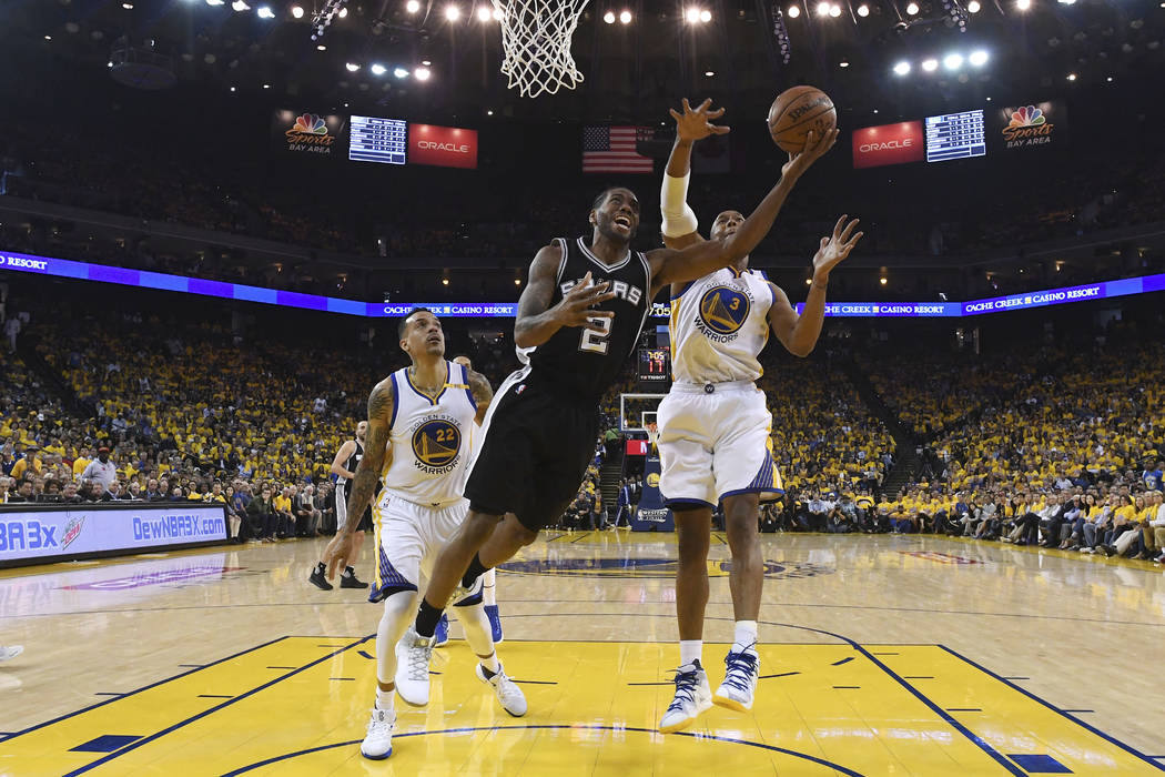 San Antonio Spurs forward Kawhi Leonard (2) shoots in front of Golden State Warriors forward Matt Barnes (22) and forward David West (3) during the first half of Game 1 of the NBA basketball Weste ...
