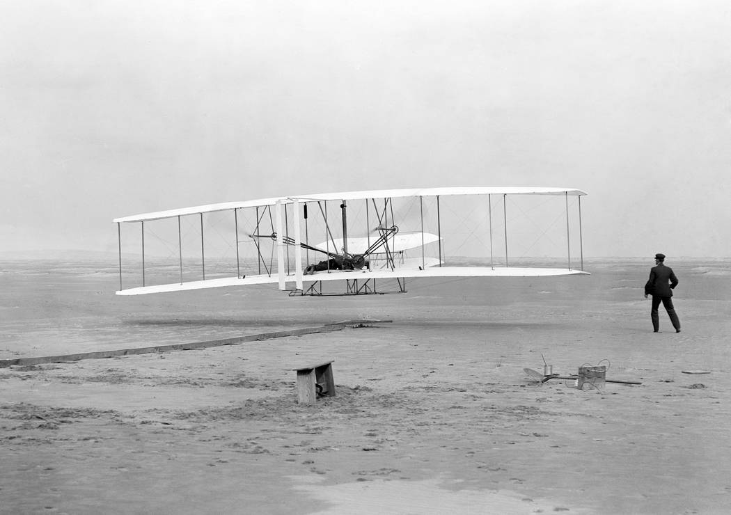 Orville Wright, lying at the controls on the lower wing, pilots  the Wright Flyer on the first powered flight by a heavier-than-air aircraft, Dec. 17, 1903, at Kitty Hawk, N.C. In the moments befo ...