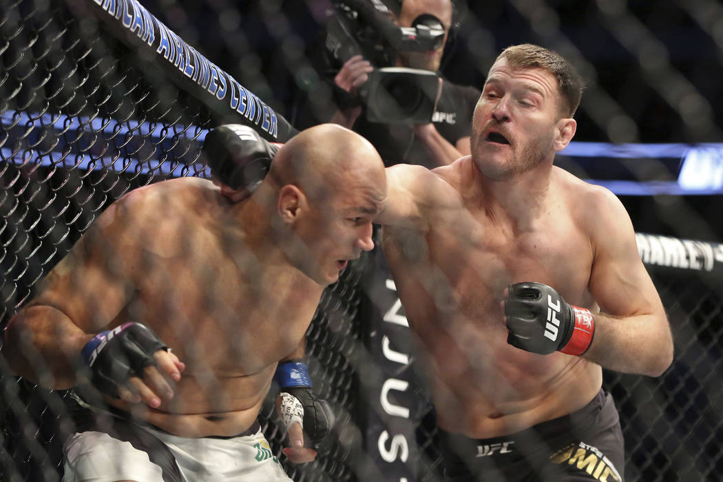 Stipe Miocic, lands a right against Junior Dos Santos in a mixed martial arts bout at UFC 211 for the UFC heavyweight championship, Saturday, May 13, 2017, in Dallas. Miocic retained his heavyweig ...