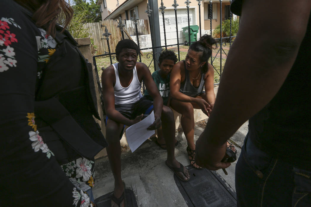 Miami-Dade Police Detective Ivette Perez, left, and a homeowner, far right, talk to suspected squatters after police removed them from a Miami house on Tuesday, April 18, 2017. Matias J. Ocner