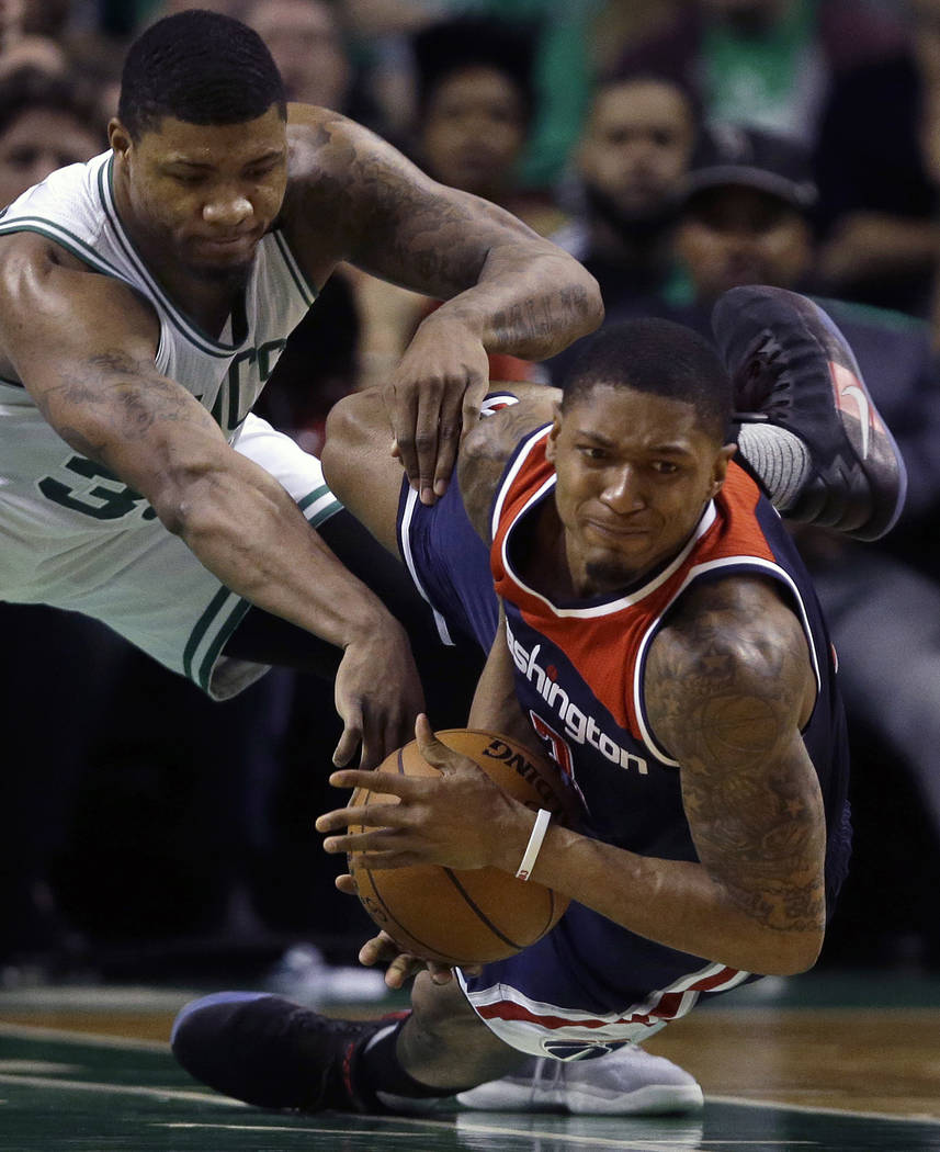 Washington Wizards guard Bradley Beal, right, goes down with the ball as Boston Celtics guard Marcus Smart defends during the second quarter of Game 7 of a second-round NBA basketball playoff seri ...