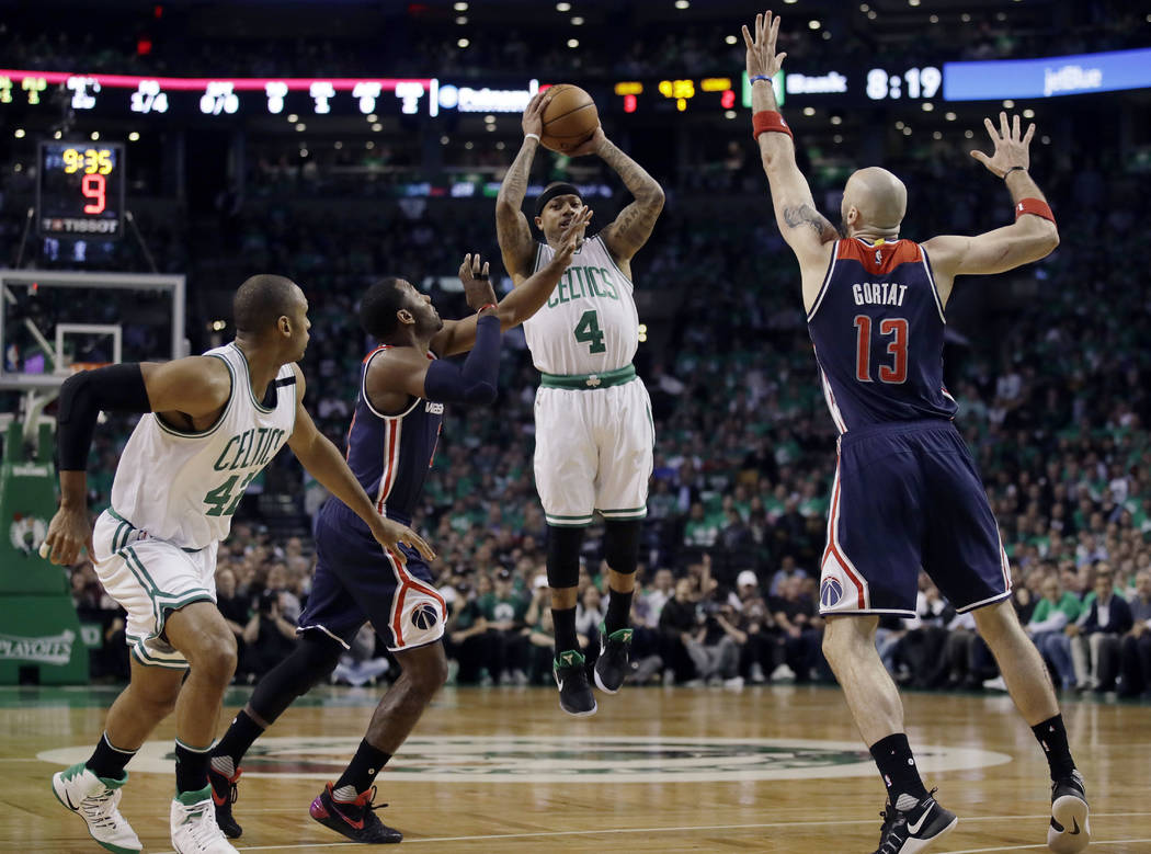 Boston Celtics guard Isaiah Thomas (4) shoots between Washington Wizards guard John Wall, left, and Wizards center Marcin Gortat (13) during the first quarter of Game 7 of a second-round NBA baske ...