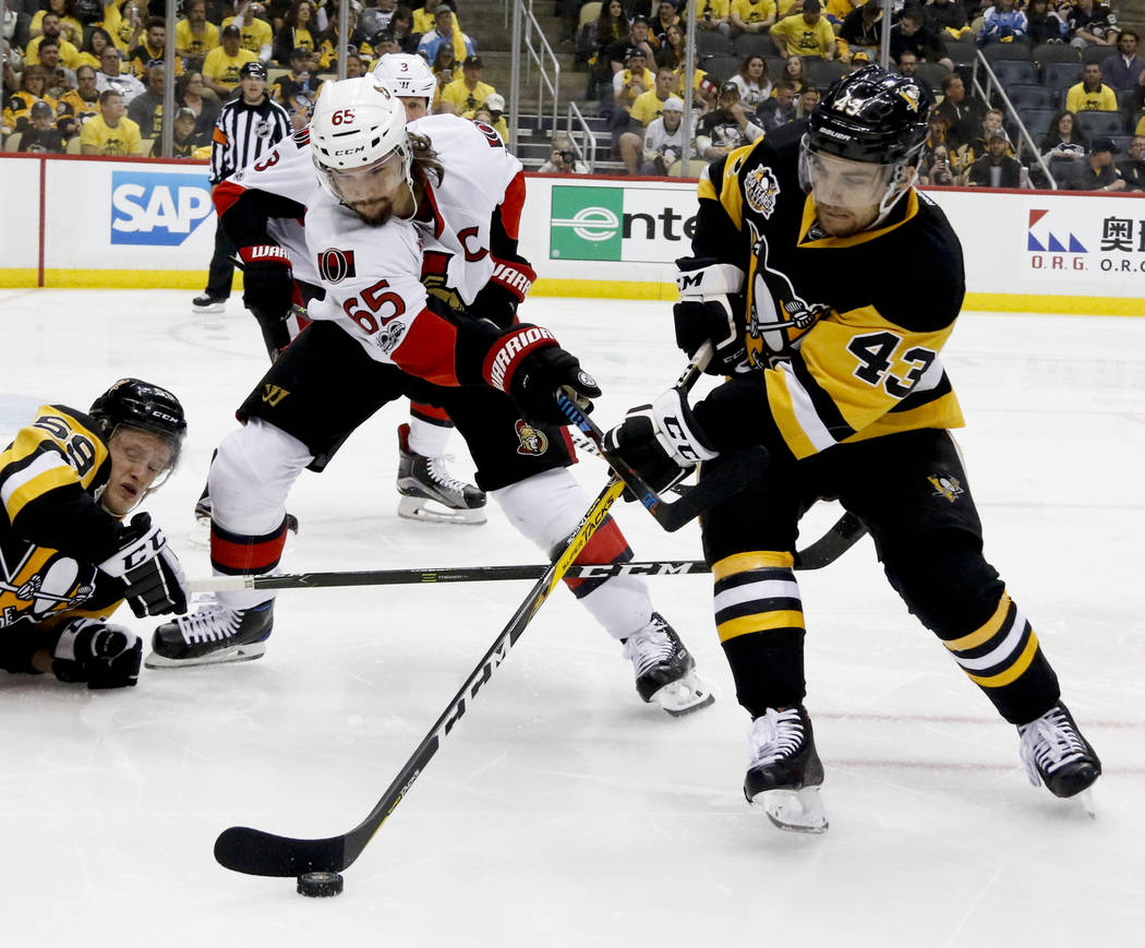Pittsburgh Penguins' Conor Sheary (43) skates away from Ottawa Senators' Erik Karlsson while Penguins' Jake Guentzel, left, is on the ice during the second period of Game 2 of the Eastern Conferen ...