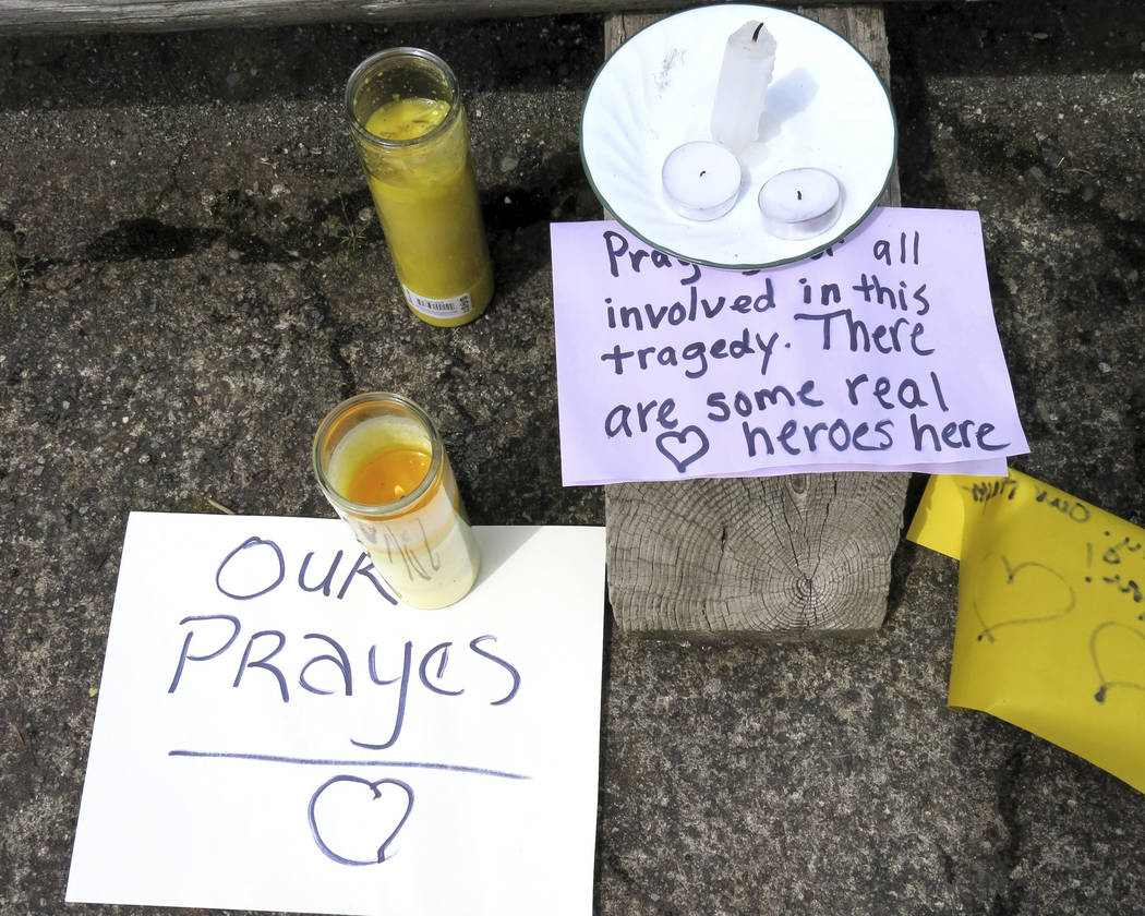 Well-wishing messages and candles for an injured employee are shown outside a grocery store in Estacada, Ore., Monday, May 15, 2017. (Gillian Flaccus/AP)