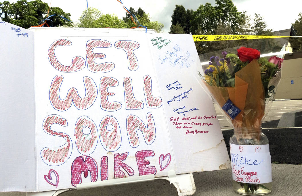 Well-wishing messages and flowers for an injured employee are shown outside a grocery store in Estacada, Ore., Monday, May 15, 2017. Police say a man carrying what appeared to be a human head stab ...