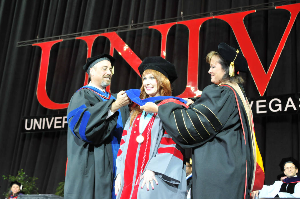 UNLV Janet King, center, takes part in a hooding ceremony for doctoral graduates during UNLV's spring commencement ceremony May 13, 2017. Putting on King's hood is Dr. Kendall Hartley, left, and D ...