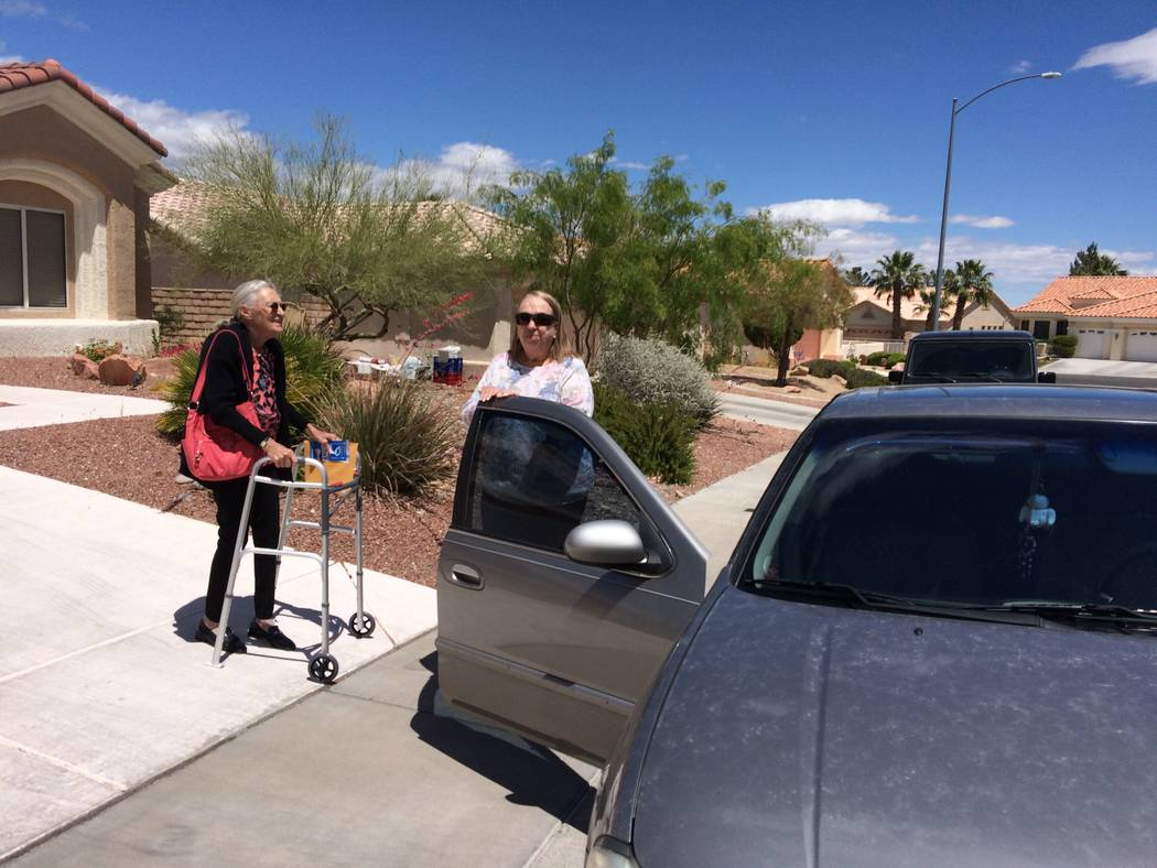 Rosalund Lang, 74, uses a walker to approach Janet Parker, a volunteer with Sun City Summerlin Charities. Rosalund broke her back - her body brace evident beneath her clothes - so she relies on th ...