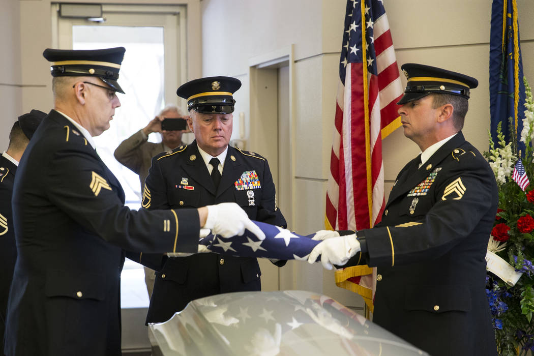 The U.S. Army National Guard Honor Guard members from left, Sgt. Nicolas Gonzales, Sfc. Shawn Fidler, and Sfc. Johnson Patrick fold an American flag during the funeral for Korean War soldier Pfc.  ...