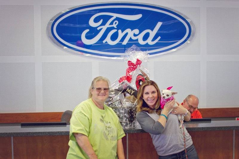 Friendly Ford Paws for the Cause founder Dana Arcana, right, is about to give a 7-month-old Chihuahua to Robin McCandlish, who adopted the dog May 13 at Friendly Ford, 660 N. Decatur Blvd.