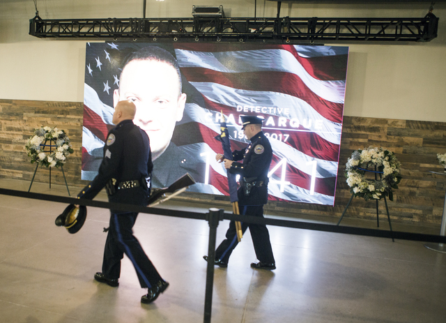 Police officers walk past a screen showing an image of  North Las Vegas police detective Chad Parque Tuesday, Jan. 17, 2017, at Central Christian Church in Henderson. (Jeff Scheid/Las Vegas Review ...