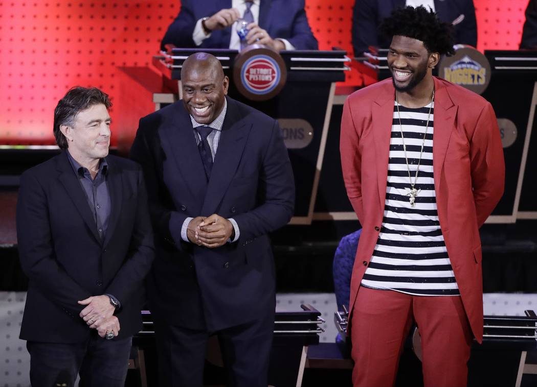 Boston Celtics co-owner Wyc Grousbeck, left, Magic Johnson, president of basketball operations for the Los Angeles Lakers, center , and Philadelphia 76ers' Joel Embiid, right, react after the lear ...