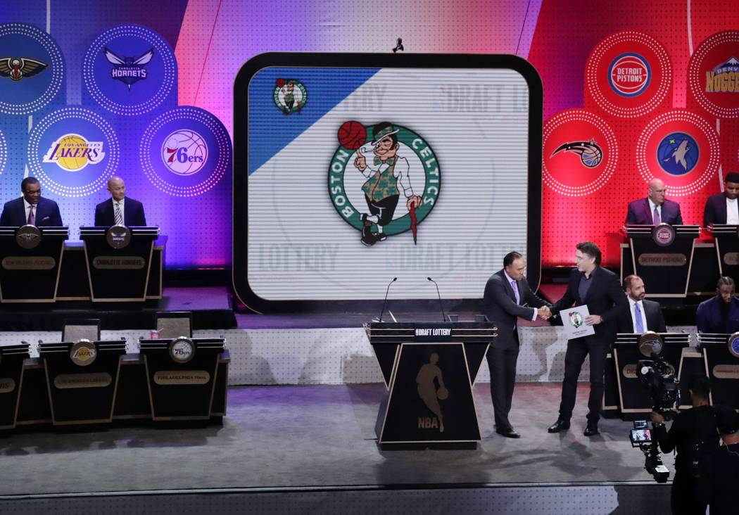 NBA Deputy Commissioner Mark Tatum, front left, shakes hands with Boston Celtics co-owner Wyc Grousbeck, right, after the Celtics won the first pick at the NBA basketball draft lottery Tuesday, Ma ...