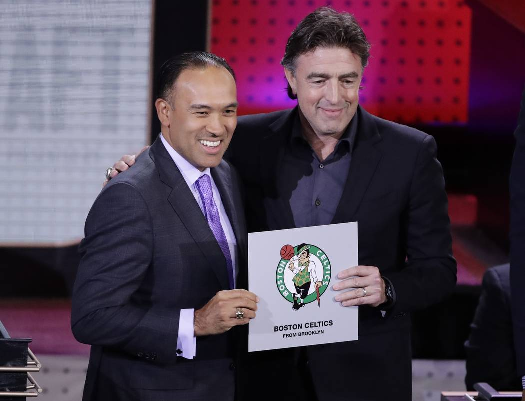 NBA Deputy Commissioner Mark Tatum, left, poses for photographs with Boston Celtics co-owner Wyc Grousbeck, right, after the Celtics won the first pick in the NBA basketball draft, at the draft lo ...