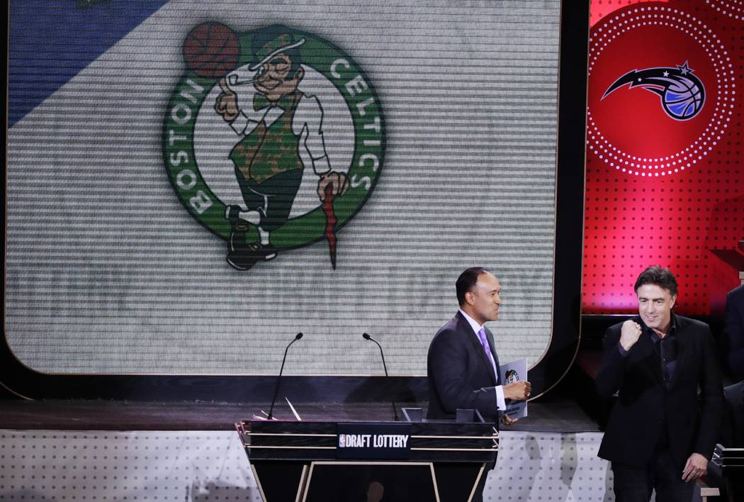NBA Deputy Commissioner Mark Tatum, left, watches as Boston Celtics co-owner Wyc Grousbeck, right, reacts after the learning the Celtics had won the first pick in the NBA basketball draft, at the  ...