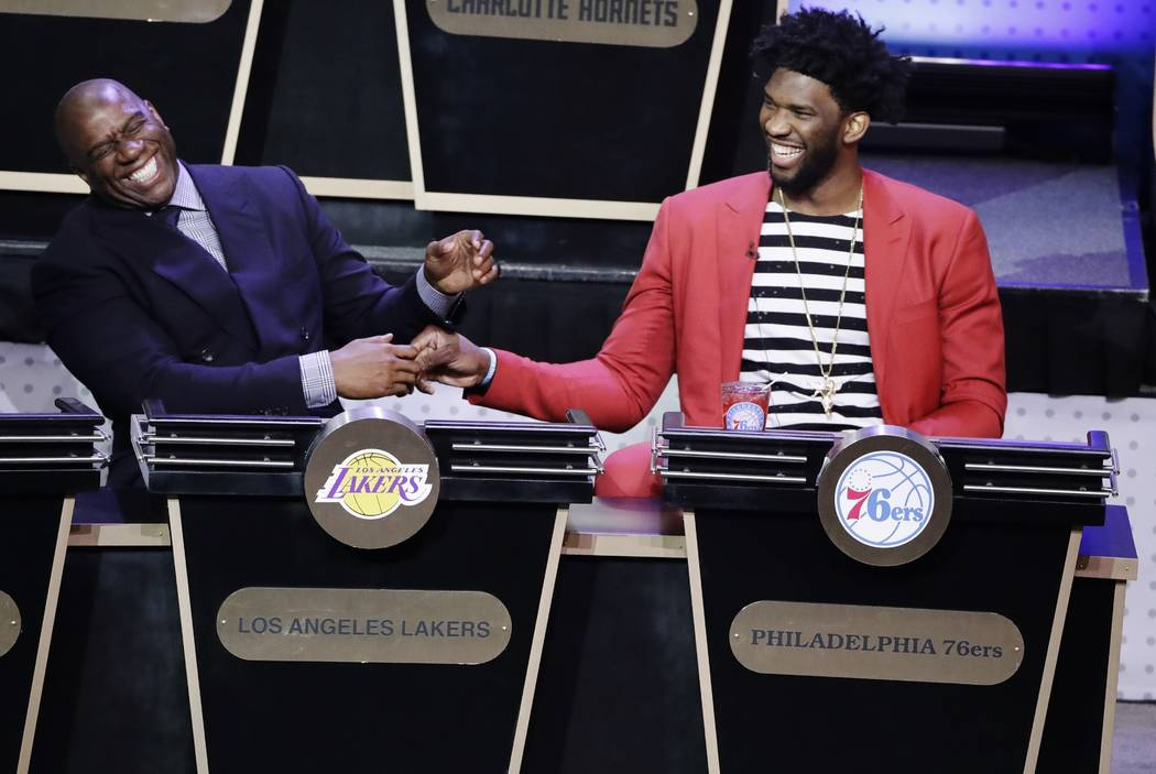 Magic Johnson, president of basketball operations for the Los Angeles Lakers, left, and Philadelphia 76ers' Joel Embiid, right, share a laugh as the results of the NBA basketball draft lottery are ...