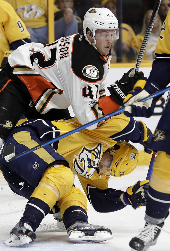 Anaheim Ducks defenseman Josh Manson (42) checks Nashville Predators left wing Viktor Arvidsson, of Sweden, below, during the second period in Game 3 of the Western Conference final in the NHL hoc ...