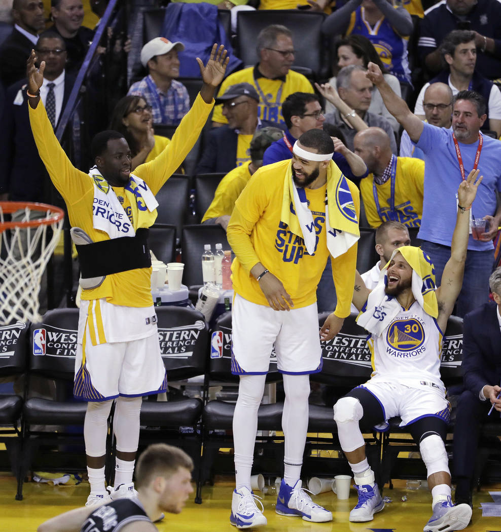 Golden State Warriors' Draymond Green, JaVale McGee and Stephen Curry, from left, celebrate from the bench in the closing minutes of the team's 136-100 win over the San Antonio Spurs during Game 2 ...